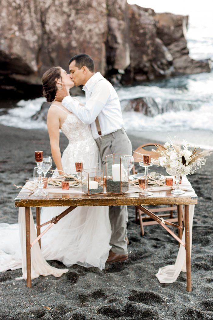Groom Kissing Real Bride at Wooden Sweetheart Table at Black Sand Beach Elopement Reception
