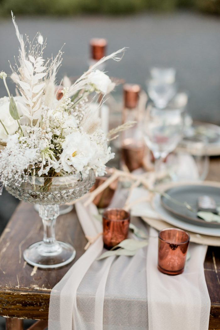 Wooden Table with Golden Candles, Glass Cups, and Floral Centerpieces