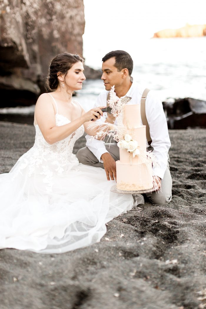 Groom Holding Cake While Bride Cuts Wedding Cake at Intimate Beach Elopement Reception
