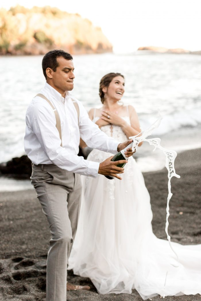 Groom Popping Open Bottle of Champagne on Beach for Wedding Toast While Bride Laughs