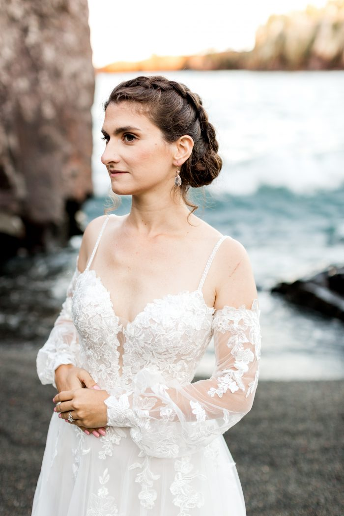 Real Bride on Black Beach Wearing Sleeved Floral Wedding Dress Called Stevie by Maggie Sottero