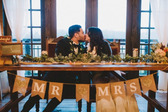 Bride and Groom Kissing While Sitting at Table with DIY Mr. and Mrs. Sign