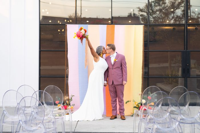 Groom Kissing Bride at Colorblock Wedding While Bride Raises Arm with Bouquet