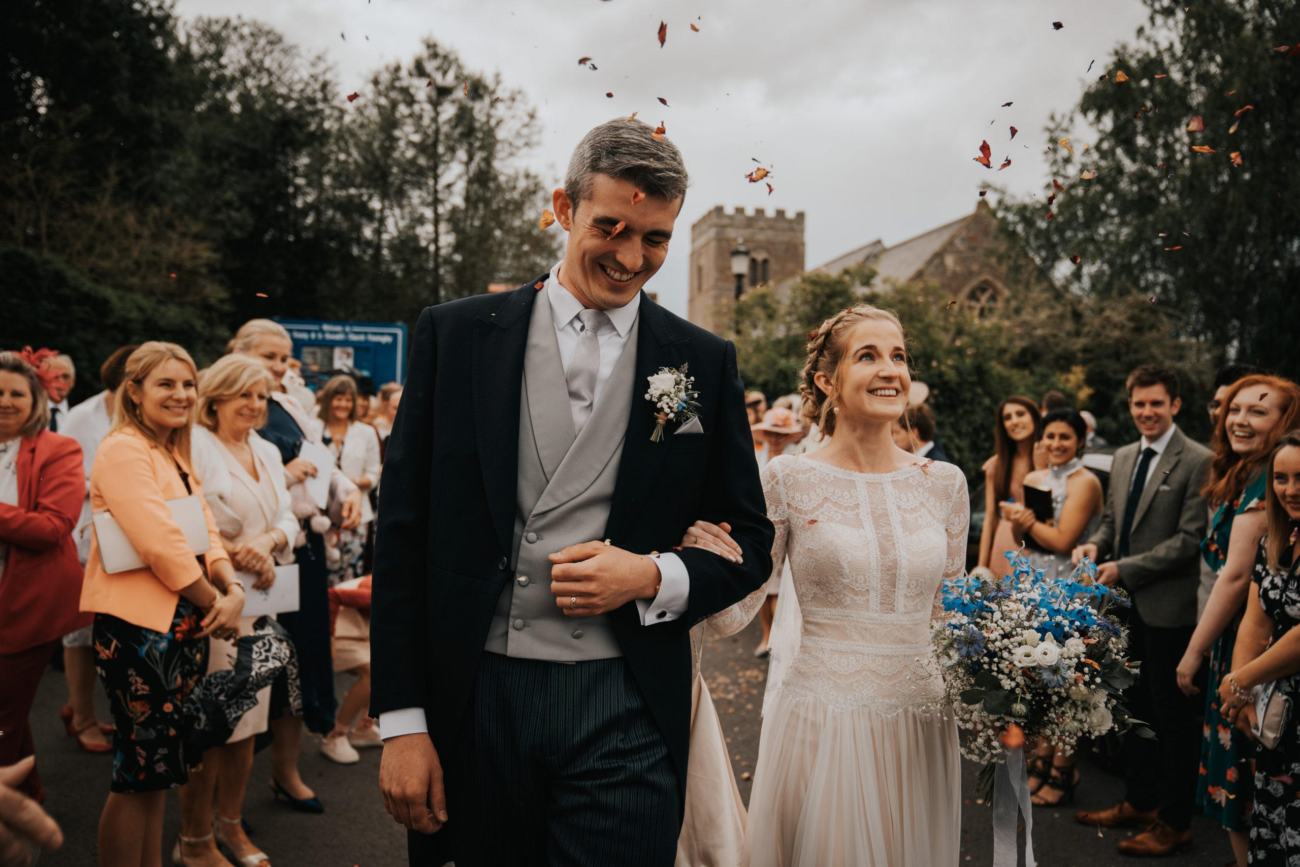 Bride and Groom Walking During Wedding Recessional While Guests Cheer