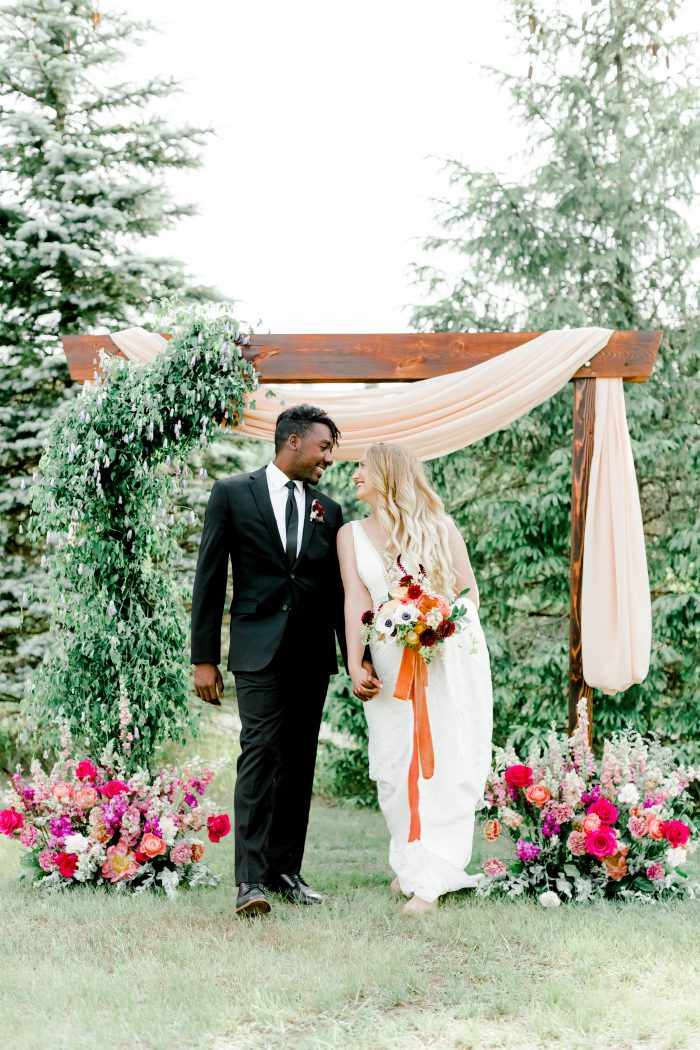 Groom Walking Under DIY Wooden Wedding Arch with Real Bride Wearing Boho Wedding Dress Called Burke by Maggie Sottero