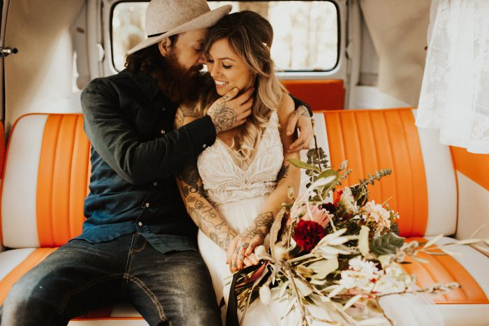Bride and Groom Sitting in Orange Camper Van While Bride Wears Boho Wedding Dress by Maggie Sottero
