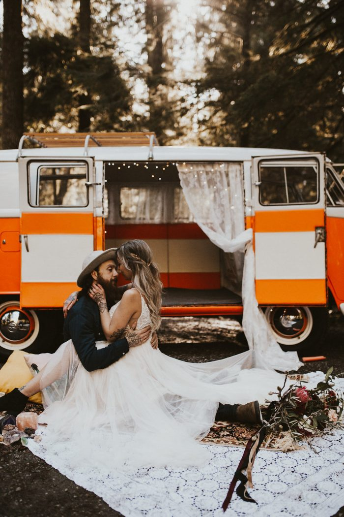 Groom Sitting in Front of Hippie Van with Bride Wearing Boho Bridal Gown Called Charlene by Maggie Sottero