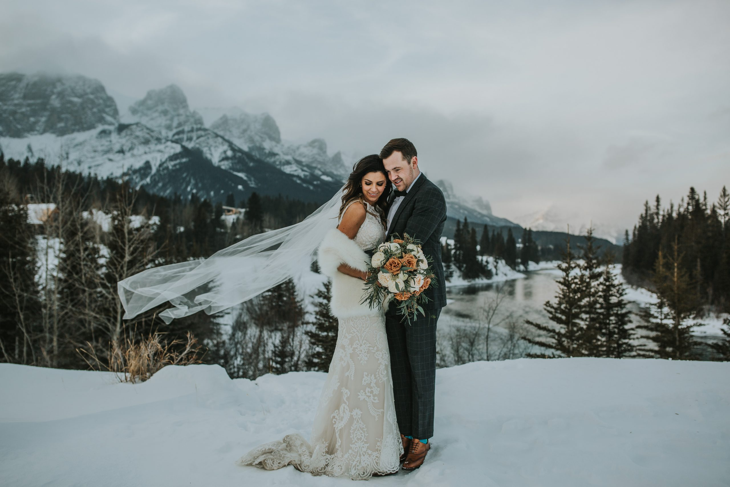 Couple in Wedding Pose in the Mountains While Bride Wearing a Lace Wedding Dress Called Winifred by Sottero and Midgley
