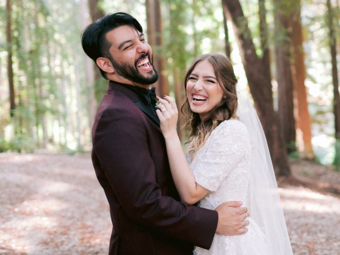 Groom Laughing Candidly with Bride Wearing Modest V-neck Wedding Dress Called Meryl Marie by Maggie Sottero