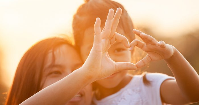 Asian mother and daughter making heart shape with hands together