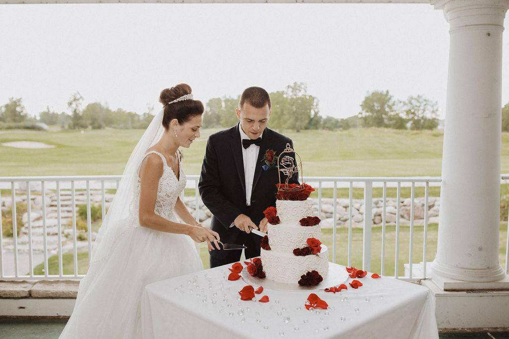 Bride and Groom Cutting Beauty and the Beast Themed Wedding Cake