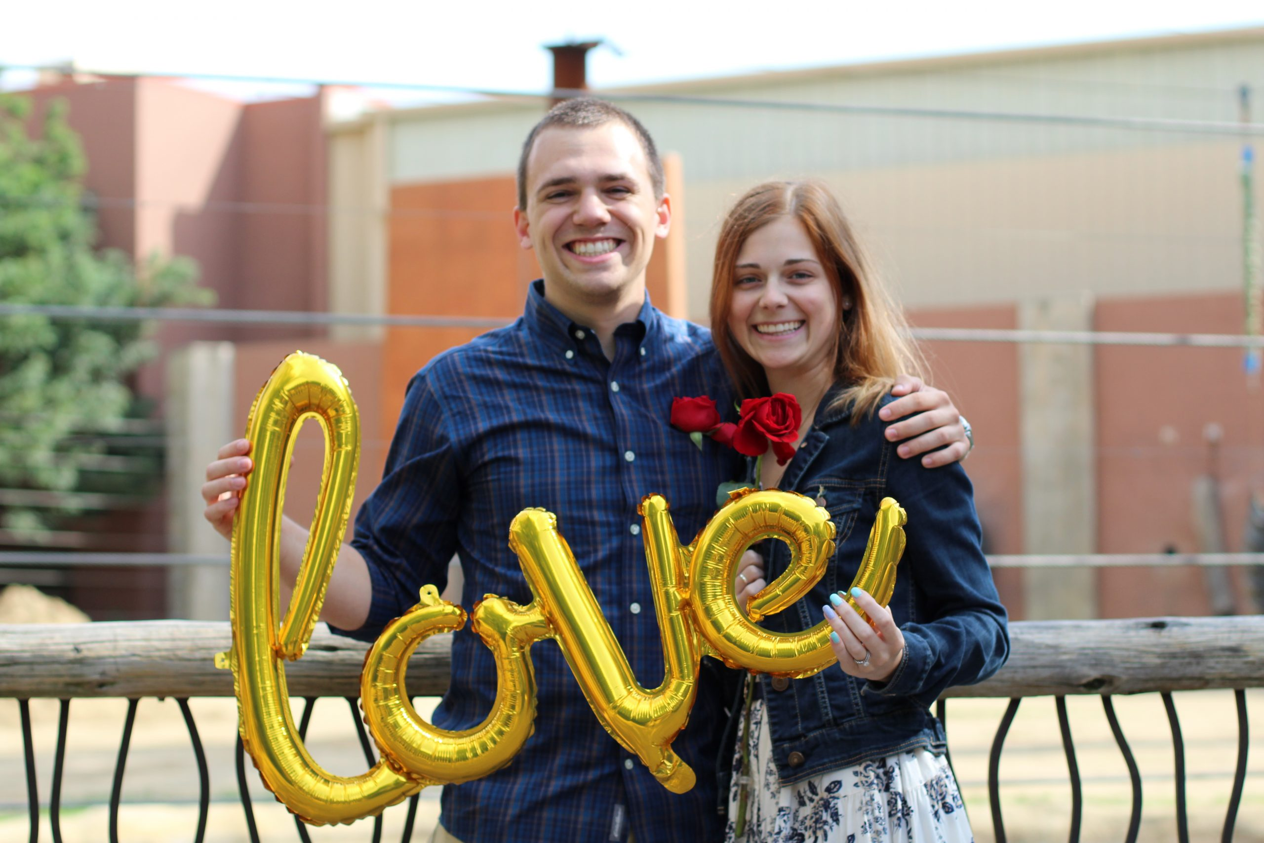 Fiance with His Fiancee Holding Up Balloons that Spell Love After Getting Engaged