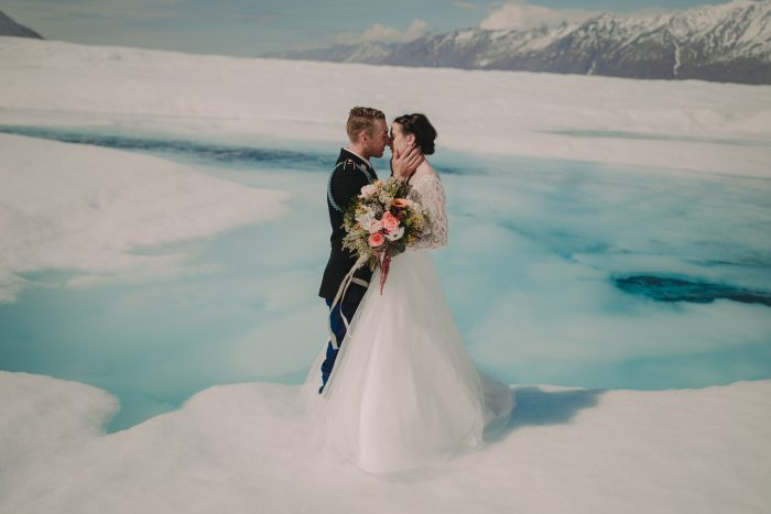 Groom Kissing Real Bride Wearing Maggie Sottero Wedding Gown on Glacier During Winter Elopement