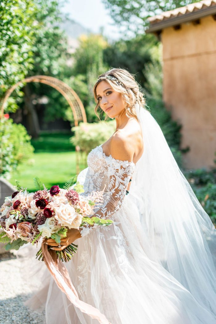 Model Wearing Floral Off-the-Shoulder Sleeve Ball Gown Wedding Dress Called Orlanda by Maggie Sottero