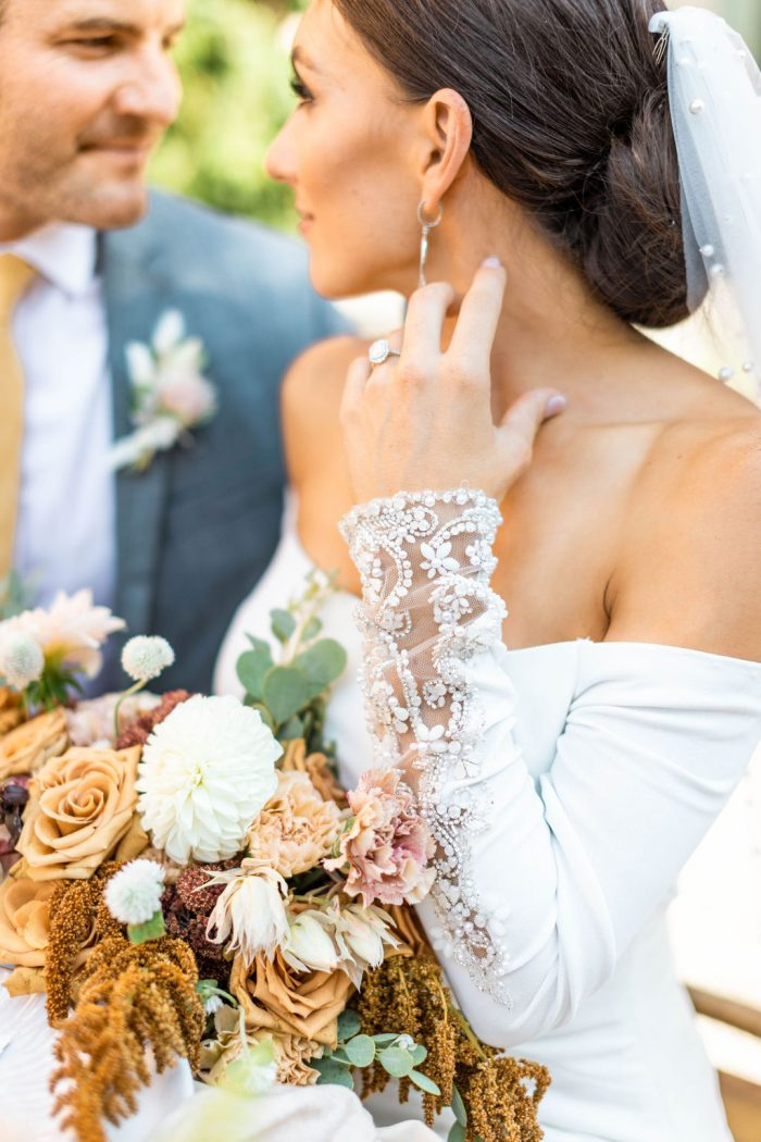 Groom Sitting at Italian Wedding with Bride Wearing Off-the-Shoulder Crepe Wedding Dress Called Admina by Sottero and Midgley