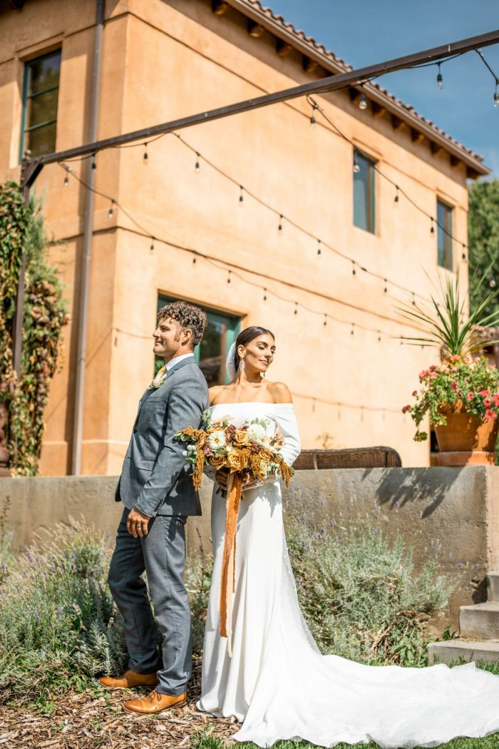 Groom Standing in Front of Tuscan Villa Wedding Venue with Real Bride Wearing Modern Crepe Wedding Dress Called Admina by Maggie Sottero