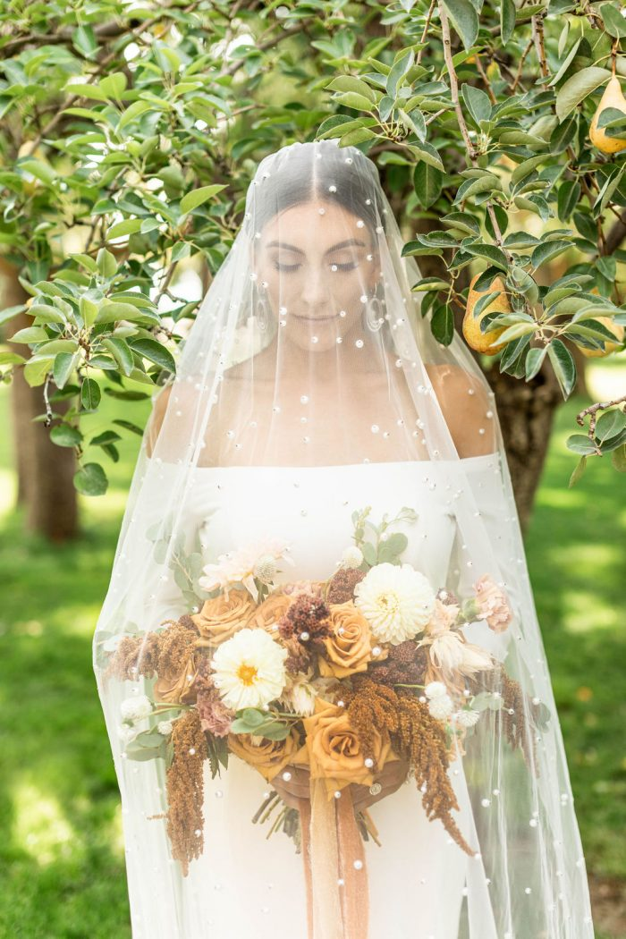 Real Bride Holding Bouquet and Wearing Cathedral Wedding Veil with Pearls Called Pierce by Sottero and Midgley