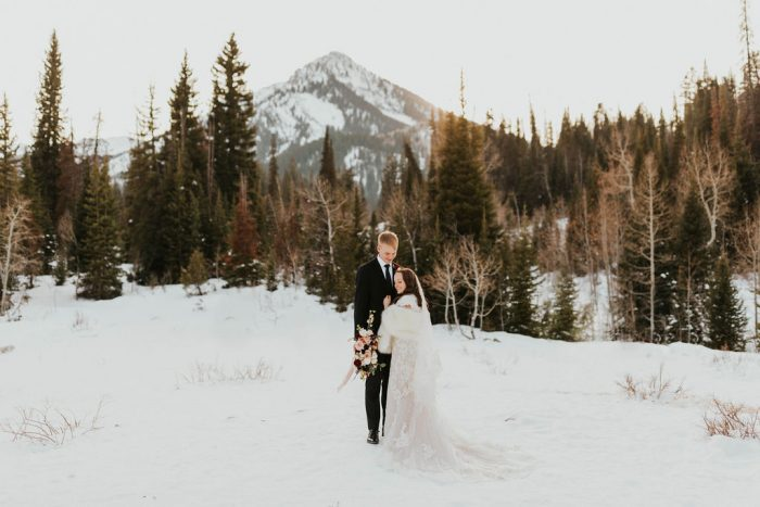 Groom in Winter Mountain Landscape with Real Bride Wearing a Fur Wrap and Modest Maggie Sottero Wedding Dress