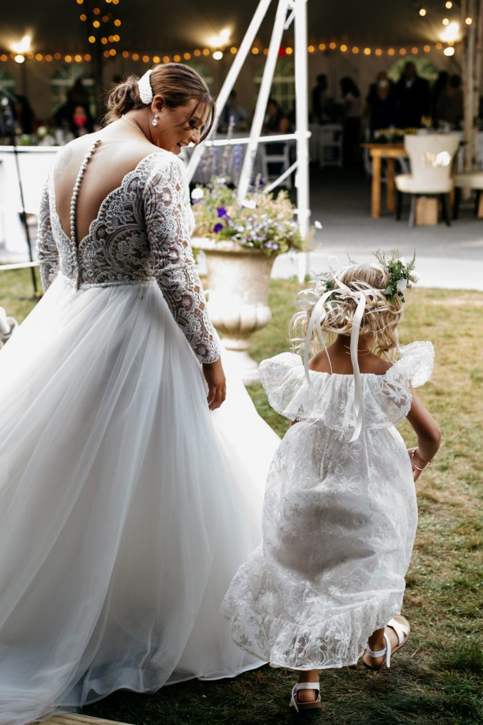 Real Bride Wearing Scallop Lace Wedding Dress Mallory Dawn by Maggie Sottero While Walking with Flower Girl
