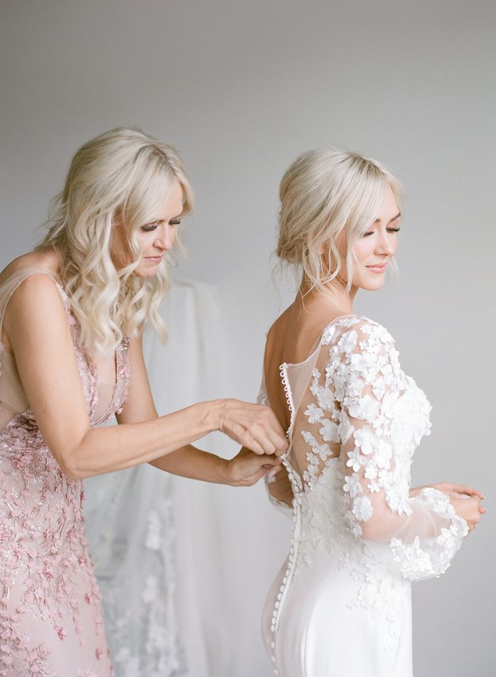 Mother of the Bride Helping Model Ashlee Jensen Wearing Custom Maggie Sottero Wedding Dress with Illusion Lace Floral Bishop Sleeves
