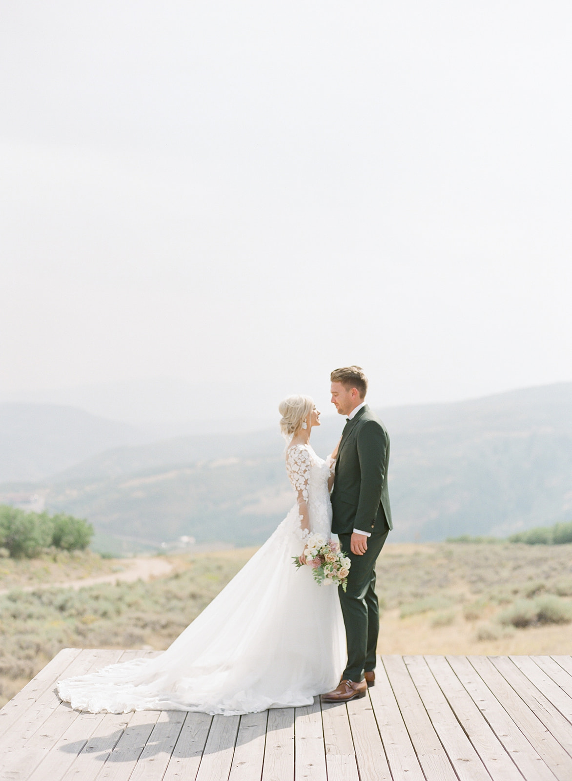 Groom with Real Bride Wearing 3-D Floral Lace Sheath Wedding Dress with Overskirt by Maggie Sottero