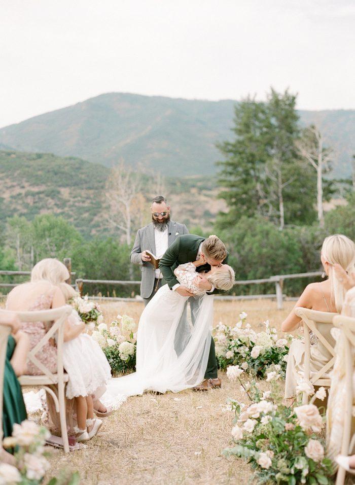 Groom Kissing Bride During Summer Wedding Ceremony