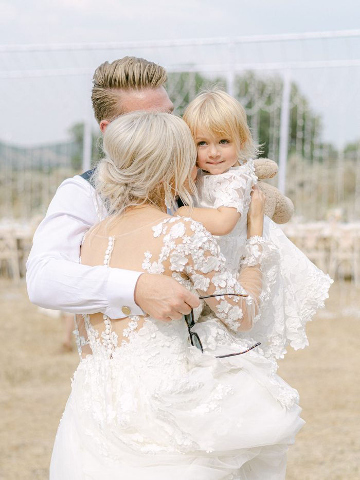 Bride Kissing Groom and Her Daughter While Wearing Custom Maggie Sottero Wedding Dress with Illusion Bishop Sleeves