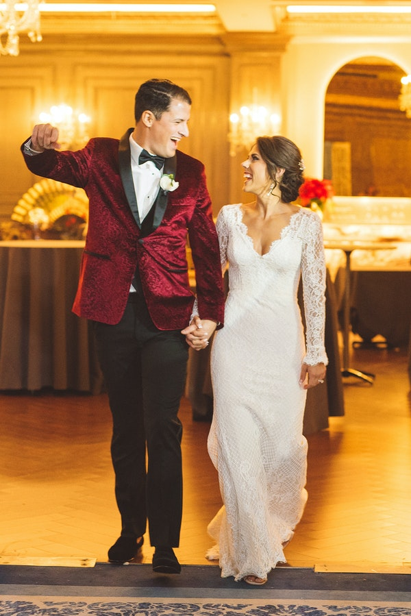 Groom in Red Tux with Real Bride Wearing Lace Sheath Winter Wedding Dress Called Antonia by Maggie Sottero