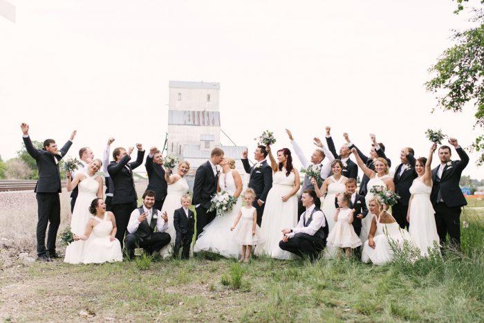Wedding Party Cheering at Real Wedding as Bride and Groom Kiss