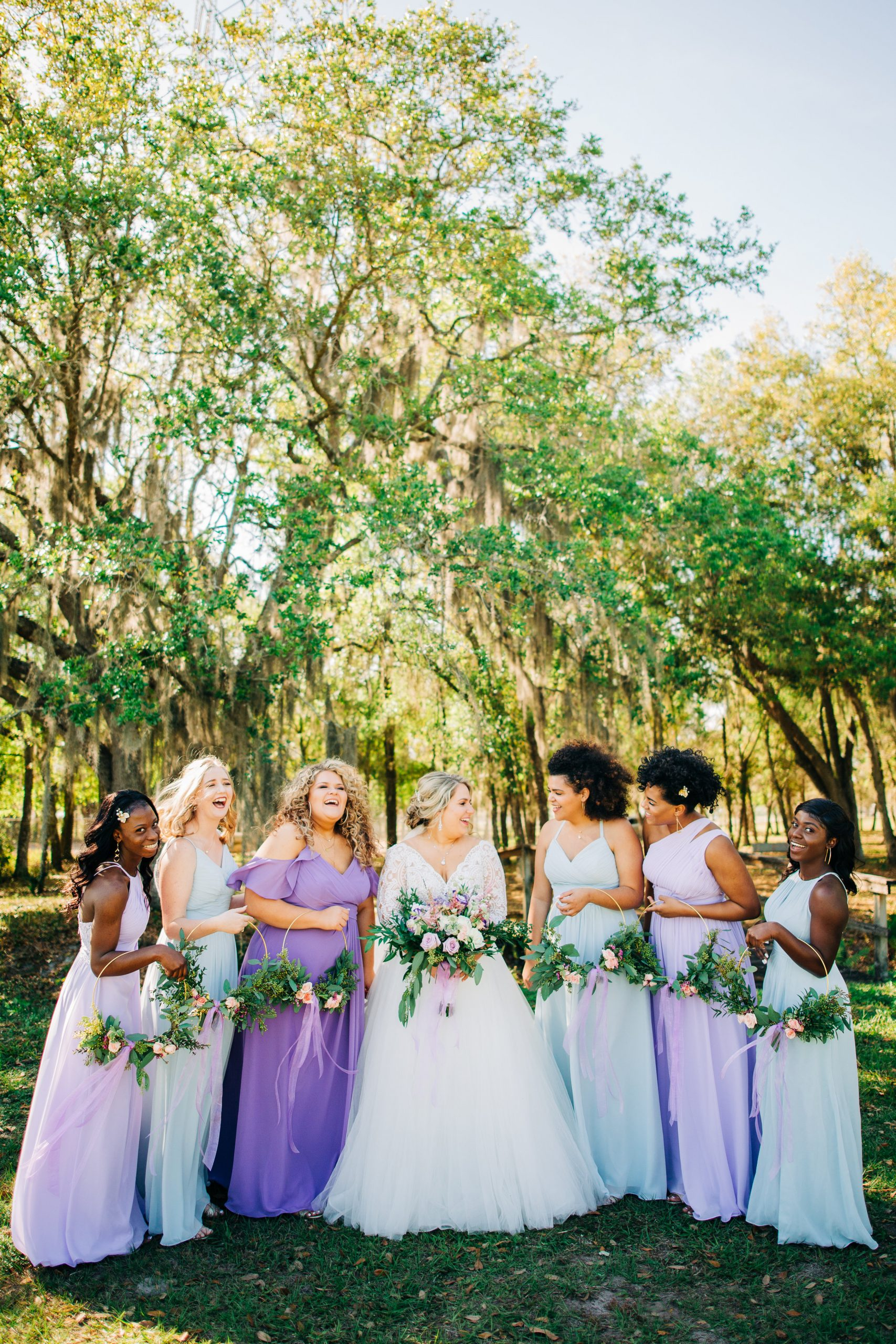Bride With Bridesmaids Wearing Pastel Purple and Blue Bridesmaid Dresses for Spring Wedding