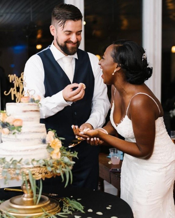 Bride and Groom eating their wedding cake wearing Nola lace sheath wedding dress by Maggie Sottero
