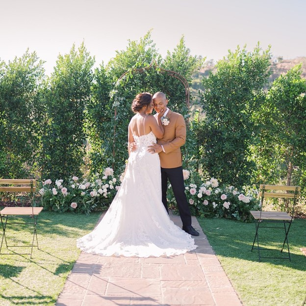 Real Bride and Groom in a Garden wearing Tuscany Lane Lace A-Line Wedding Dress by Maggie Sottero