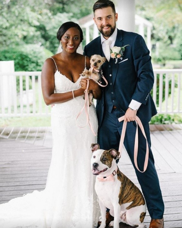 Bride and Groom holding dogs with bride wearing Nola Lace Sheath wedding gown by Maggie Sottero