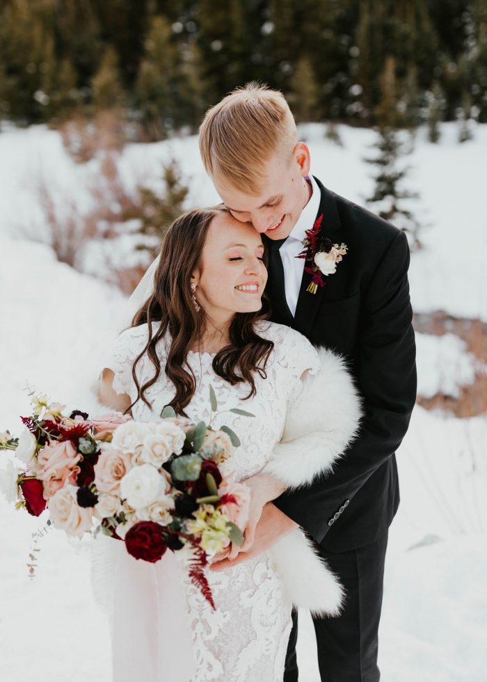 Groom at Winter Wedding with Bride Wearing Modest Lace Sheath Wedding Dress Called Tuscany Leigh by Maggie Sottero