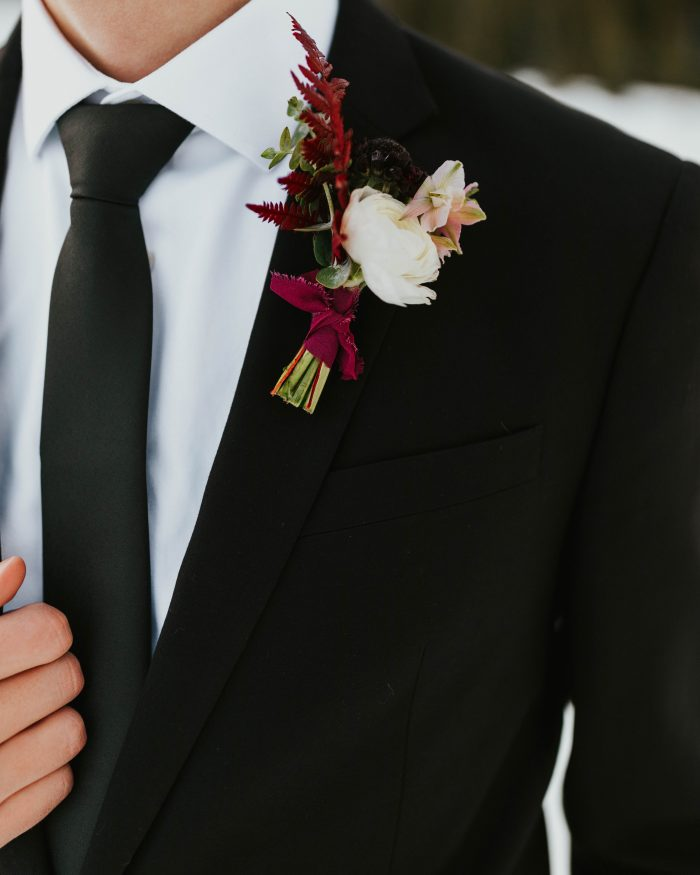 Groom Wearing Classic Black Suit and Tie with Blush and Burgundy Boutonniere
