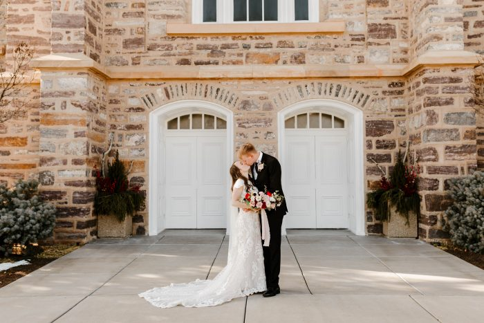 Groom Kissing Bride Wearing Modest Lace Sheath Wedding Dress Called Tuscany Leigh by Maggie Sottero