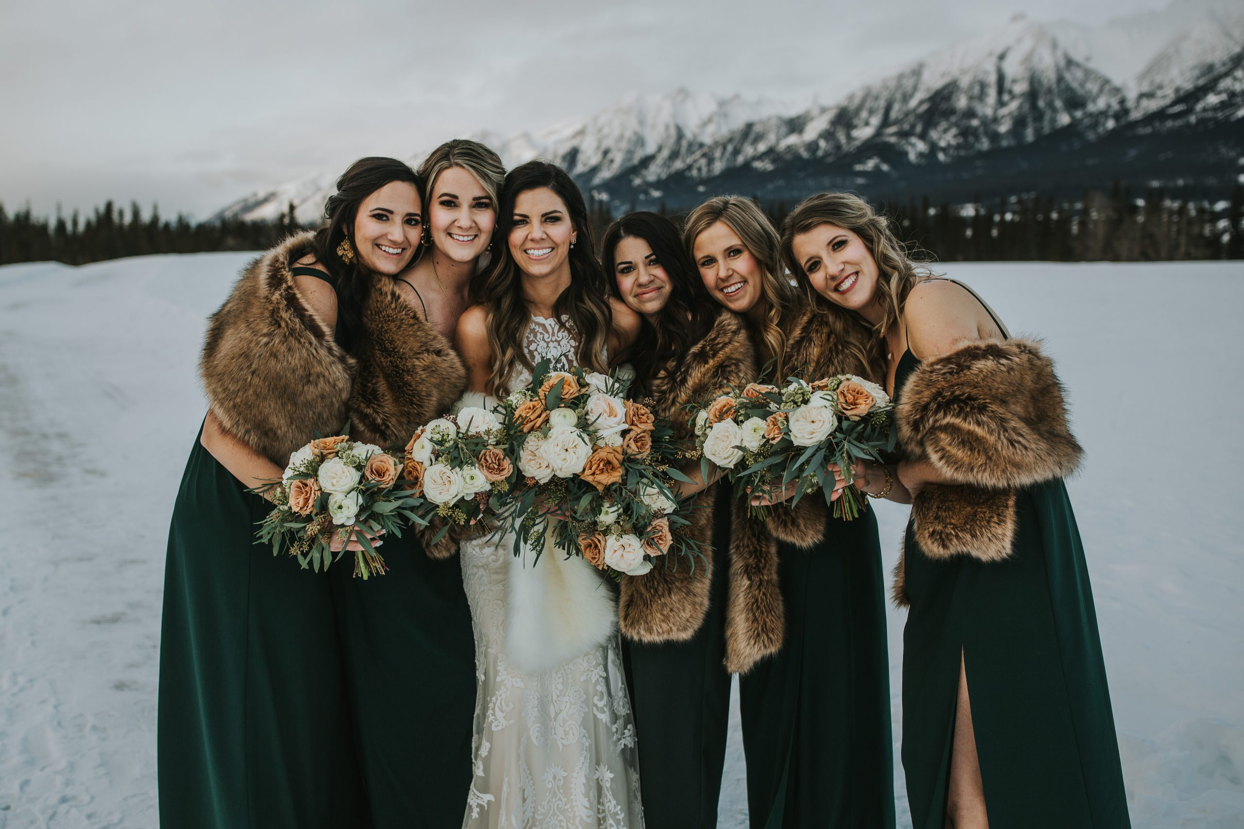 Real Bride Wearing Maggie Sottero Wedding Gown with Bridesmaids Wearing Green Velvet Dresses at Winter Wedding