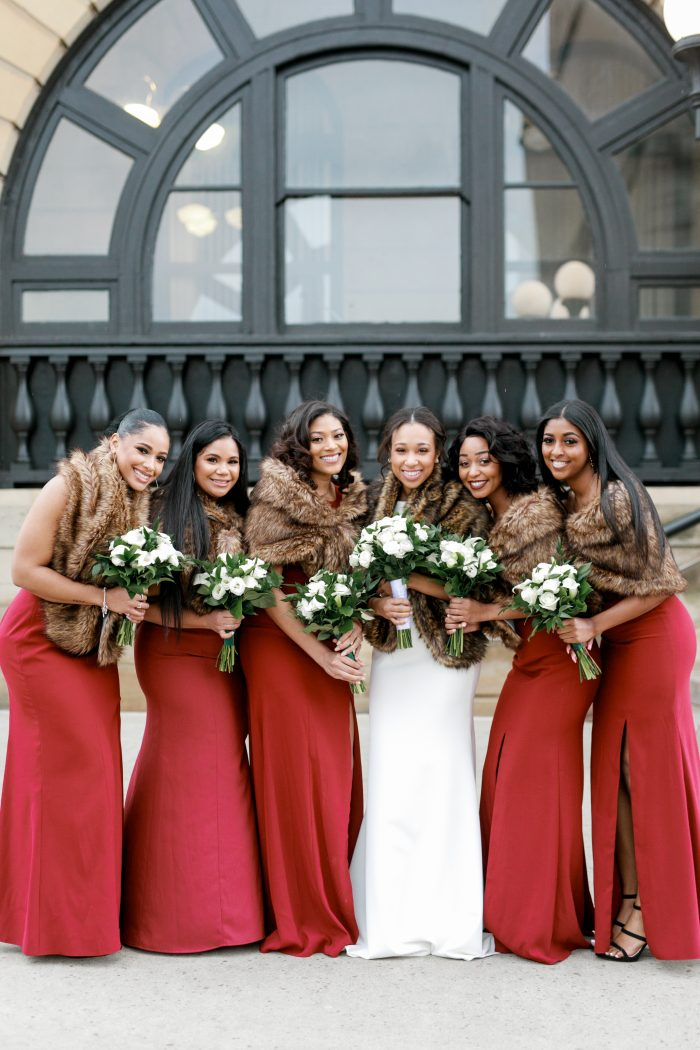 Black Bride Wearing Maggie Sottero Wedding Gown with Bridesmaids Wearing Red Dresses with Shawls for Winter Wedding