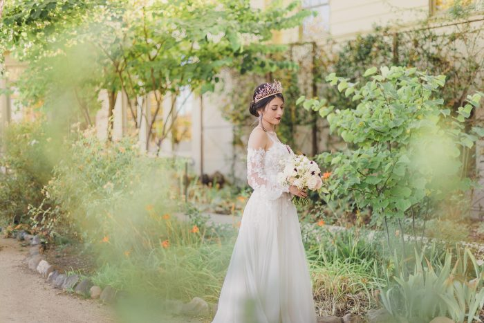 Model wearing Lace A-line Wedding Dress called Stevie by Maggie Sottero in a garden