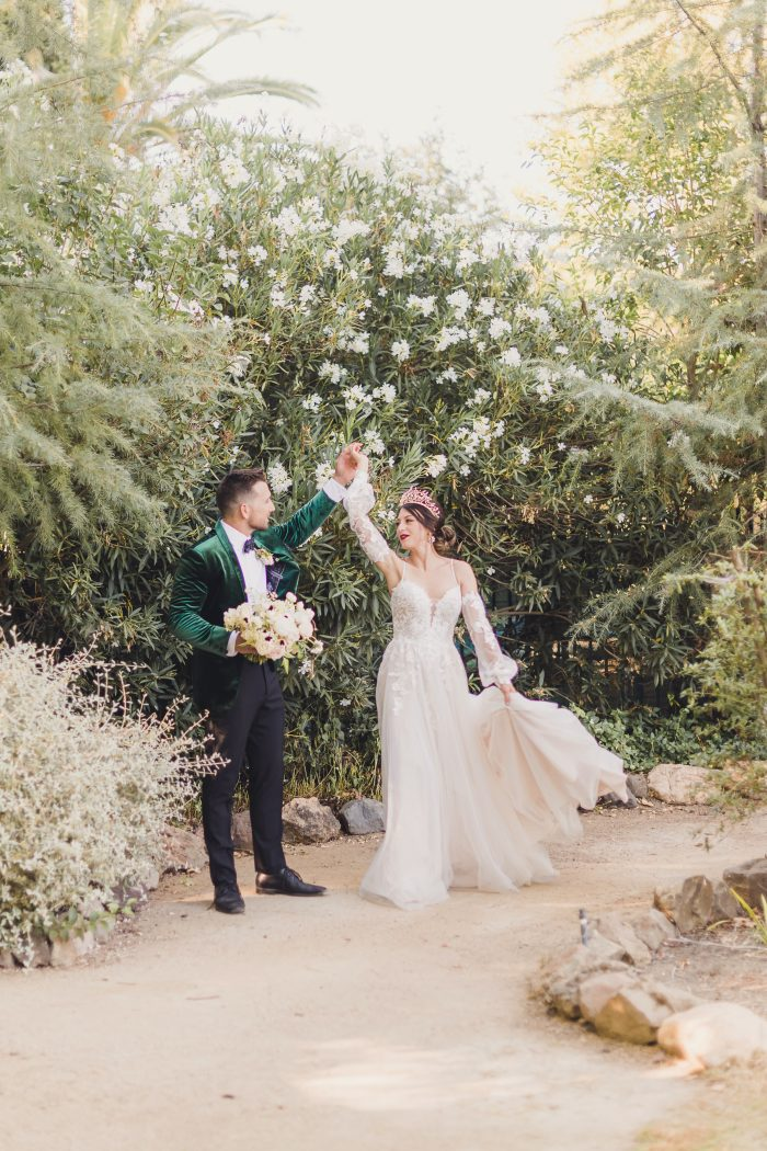 Model wearing Lace A-line Wedding Dress called Stevie by Maggie Sottero and Groom in a green velvet suit jacket in a garden