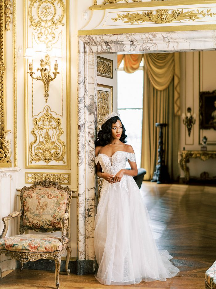 Model wearing A Garden Soiree-Ready Lace Affordable Bridal Gown Mavis by Rebecca Ingram in a Royal inspired photoshoot