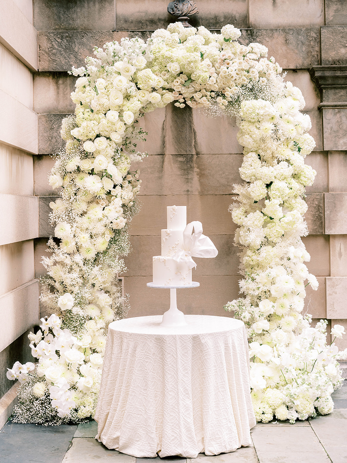 White floral arch with a white royal inspired cake inside