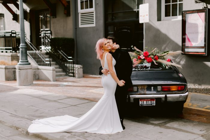 Bride Wearing Simple Mermaid wedding dress Fernanda by Maggie Sottero with her groom next to a fun decorated car