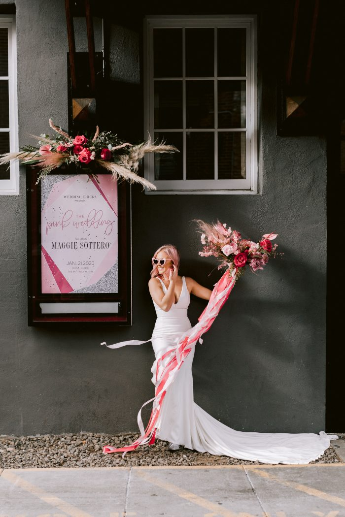 Bride wearing Simple Mermaid wedding dress Fernanda by Maggie Sottero holding a fun pink and red bouquet