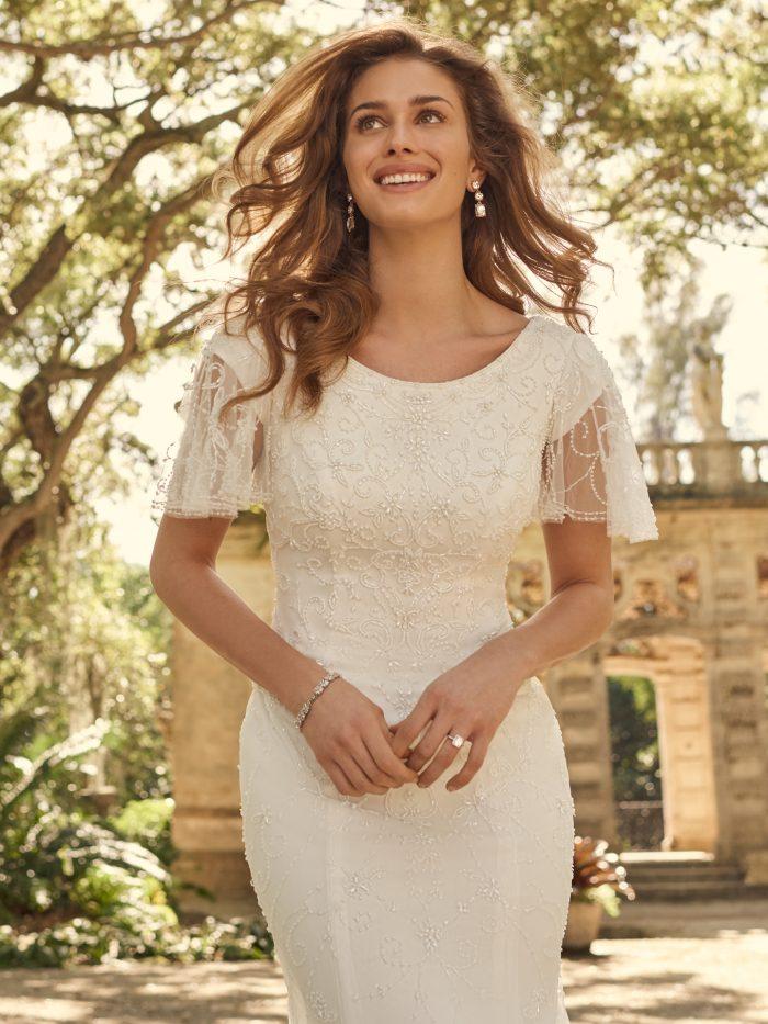 Bride Wearing Modest Flutter Sleeve Sheath Bridal Gown Called Garnett by Maggie Sottero