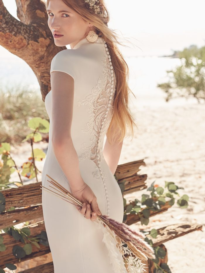 Bride on Beach Wearing Crepe Statement-Back Wedding Dress Called Carole by Maggie Sottero