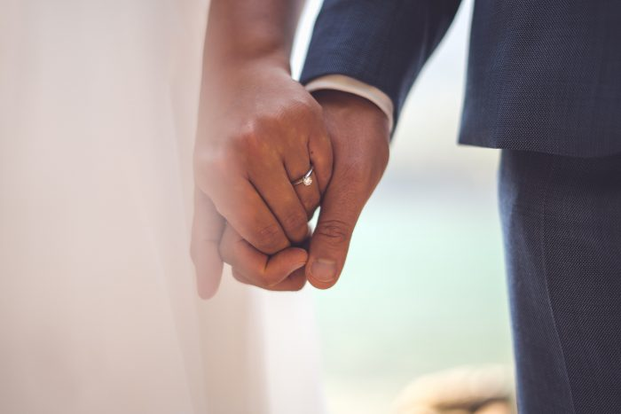Bride and Groom Wearing Wedding Rings Holding Hands on Wedding Day