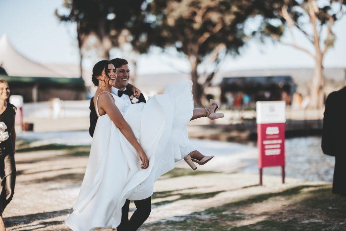 Groom Carrying Bride Wearing Satin Ball Gown Wedding Dress Called Selena by Maggie Sottero