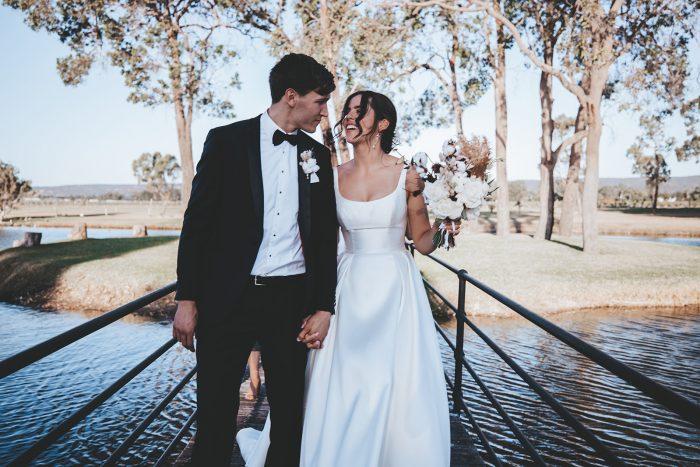 Groom Walking with Bride Wearing Modern Satin Wedding Gown by Maggie Sottero at Vineyard Wedding