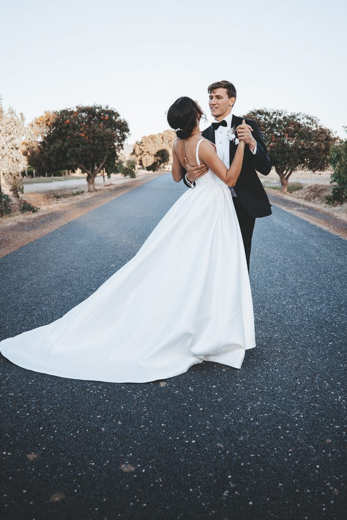 Groom Dancing with Bride Wearing Modern Satin Wedding Dress Called Selena by Maggie Sottero